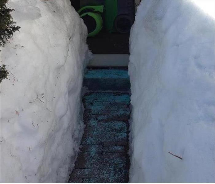 Snow banks piled high on either side of residence